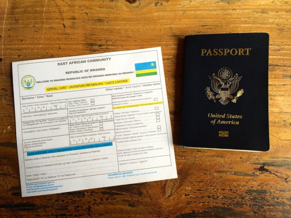 The photo shows an East African Community arrival card for Rwanda, with an American passport next to it