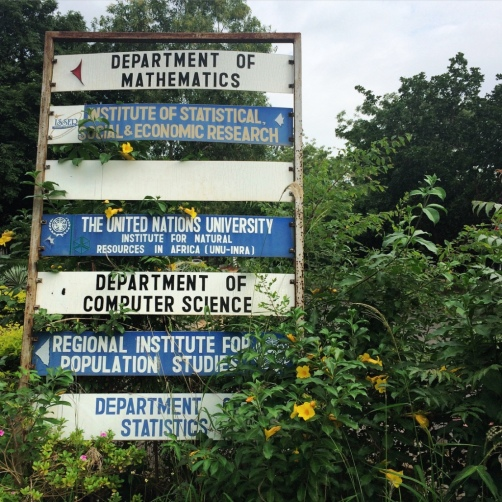 A rather overgrown sign at the University of Ghana, pointing towards the departments of math, computer sciences, and statistics