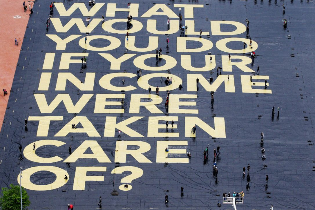 "Large sidewalk mural reading, ""What would you do if your income were taken care of?"""