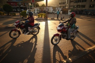 The photo shows two men driving motorcycles with the setting sun behind them in Kigali, Rwanda