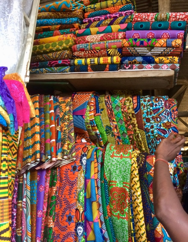 The photo shows many colorful bundles of wax print fabric on a shelf, and a woman's arm reaching up to select one