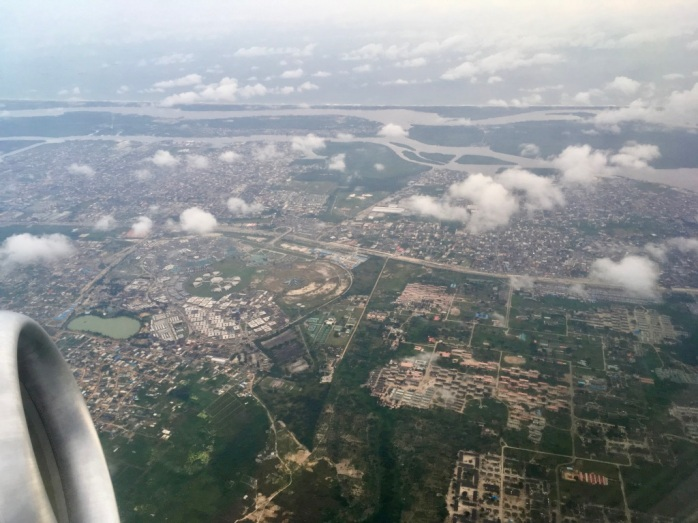 An aerial photo of Accra, showing a plane's engine, lots of green residential areas, and the coastline