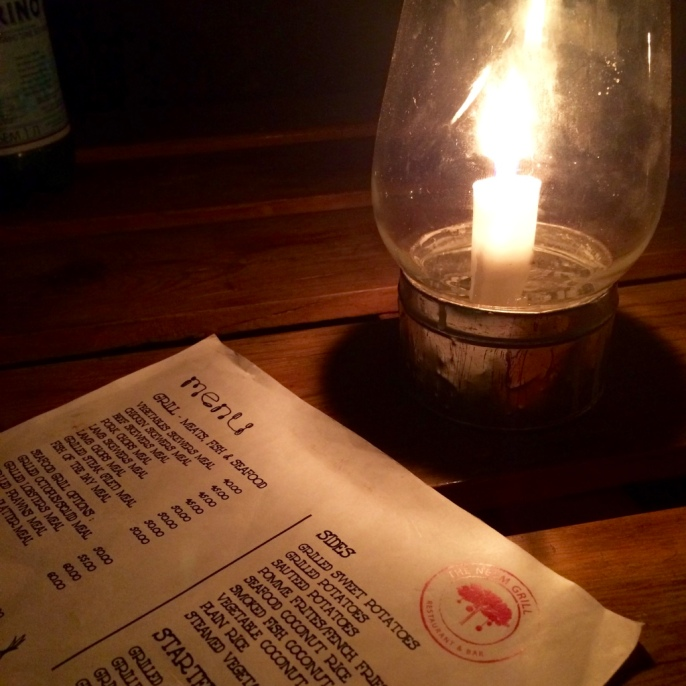The photo shows a menu on a table, dimly illuminated by a candle