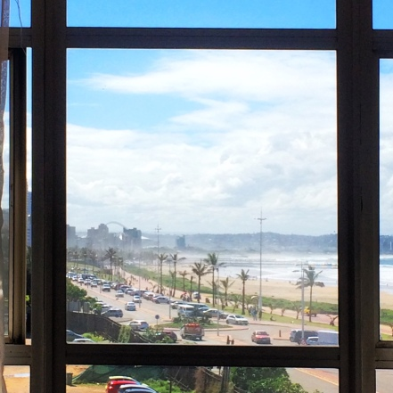The photo shows a beachfront scene, framed by a window, in Durban, South Africa