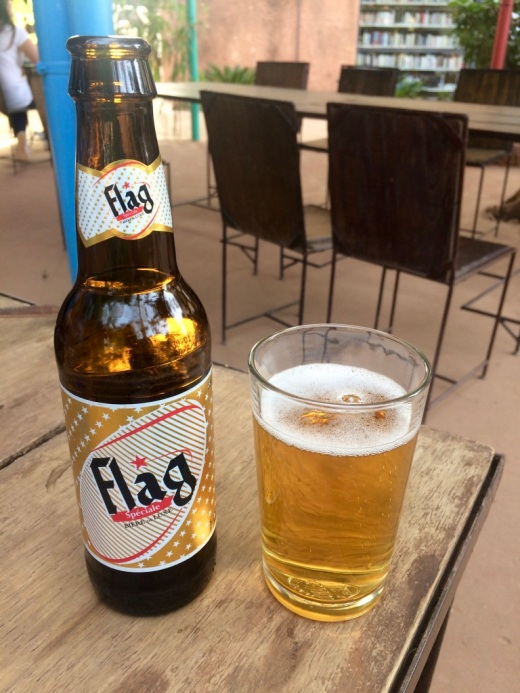 The photo shows a bottle of Flag beer sitting on an outdoor table
