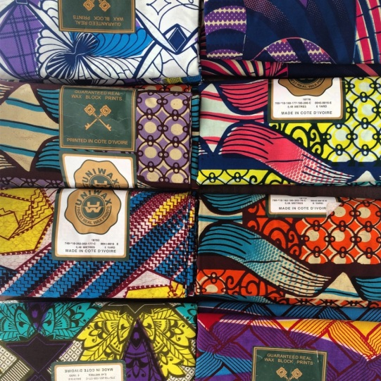 The image shows colorful wax print fabric from Burkina Faso
