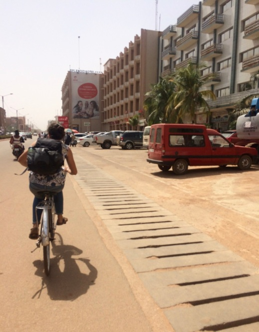 The photo shows a woman on a bicycle on one of the main streets of Ouagadougou