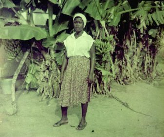 The image shows a Ghanaian woman in a white shirt and printed dress standing in front of a banana grove
