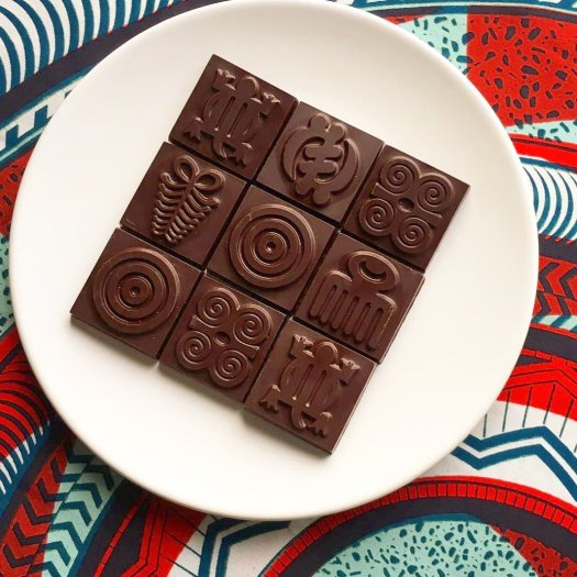 The photo shows a bar of chocolate with Ghanaian adinkra symbols printed on it
