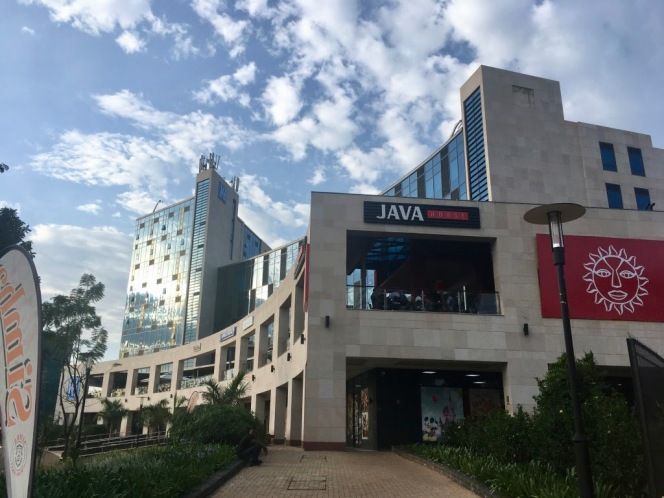 The photo shows Kigali Heights, a modern, glass-and-stone office building and shopping complex