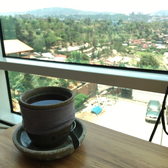 The photo shows a cup of tea on a table in front of a window, which has a view of Kigali's green hills