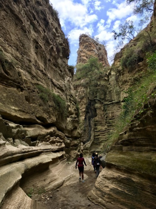The photo shows a canyon with two people walking through it, and the blue sky above