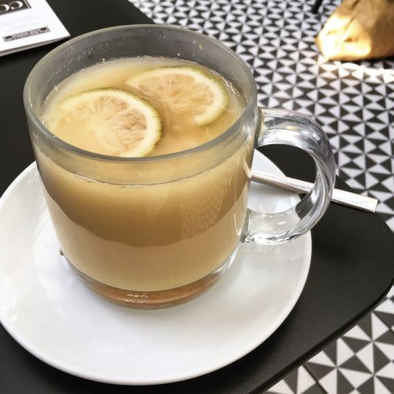 The photo shows a glass of ginger-lemon tea sitting on a black table, with a black and white checked floor visible in the background