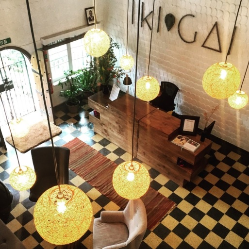 "Interior of an office space, with white brick walls and a checkered floor.  There are large yellow lamps hanging from the ceiling, and a sign saying ""Ikigai"" on one wall"