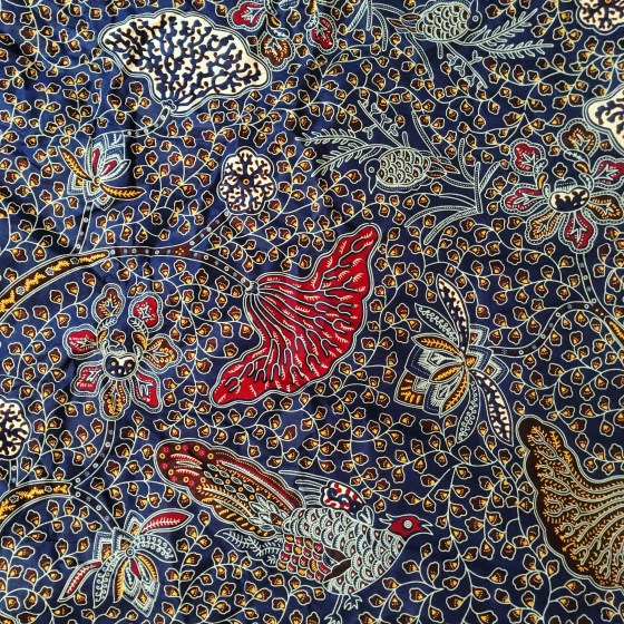 Fabric with a blue background, and colorful illustrations of birds and flowers in the foreground
