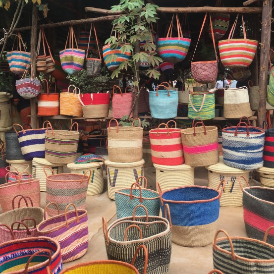Colorful woven baskets sitting on the ground and hanging from the roof of a market stall