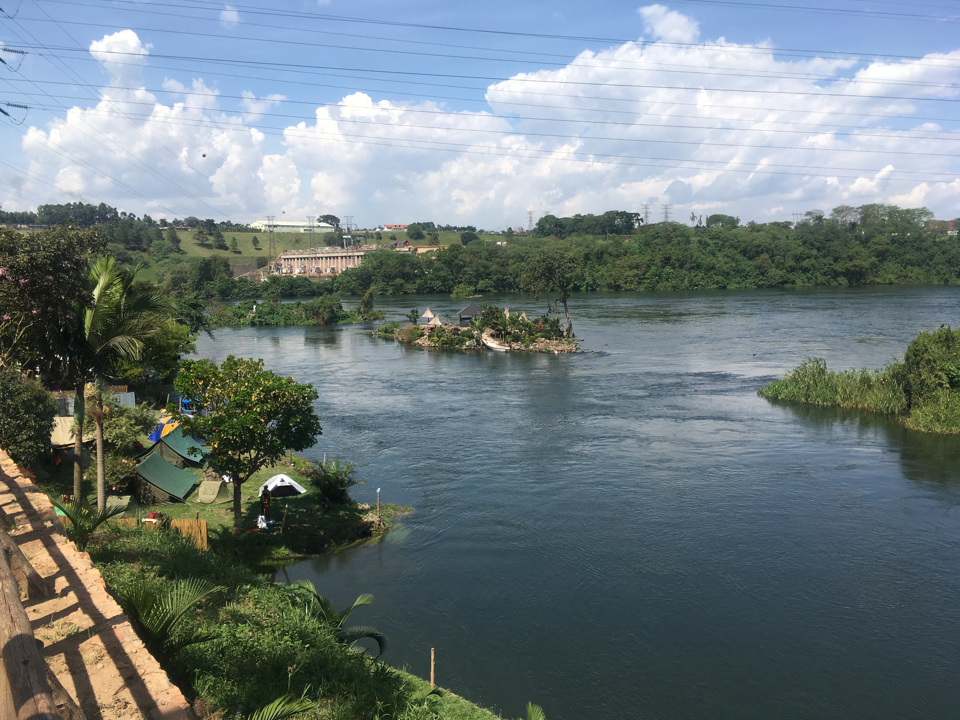 View of the Nile, with green banks on both sides and a blue sky full of puffy clouds above