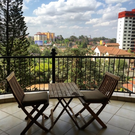 Balcony with a small wooden table and two chairs on it, and a view looking out across a leafy valley towards another high rise apartment building