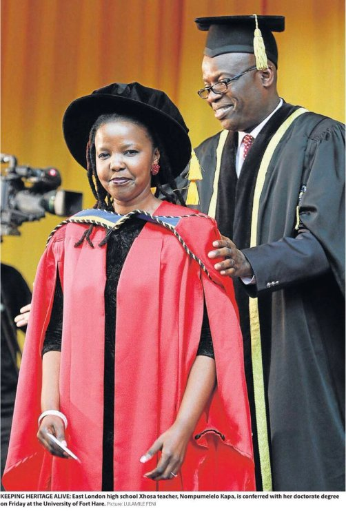 A South African woman dressed in a red gown and black velvet cap, with a South African man in a black academic robe standing behind her