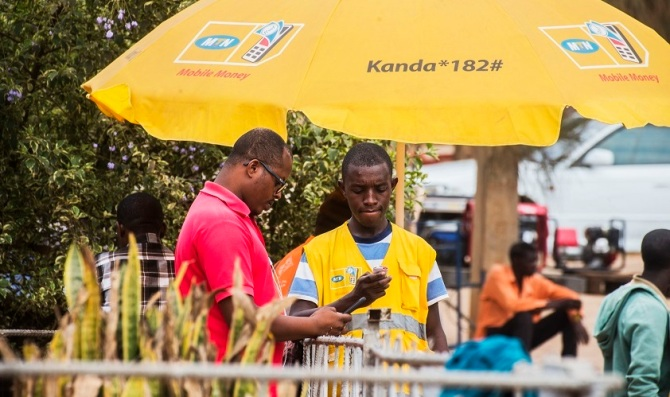 A Rwandan man in a yellow vest holds a mobile phone.  Another man in a red shirt is standing next to him.  They're both under a yellow umbrella with the MTN mobile money logo on it