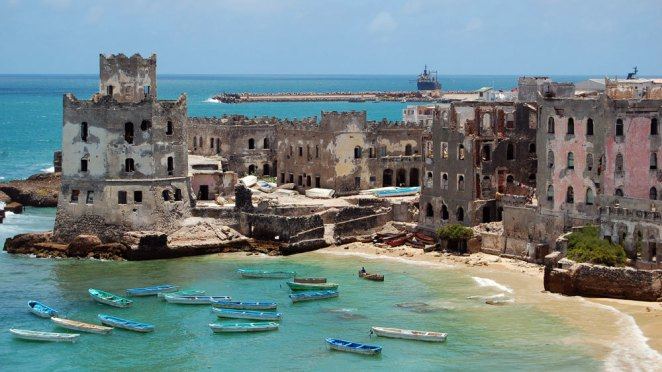 Crumbling colonial-era forts sit on the edge of a bright blue bay filled with small blue fishing boats
