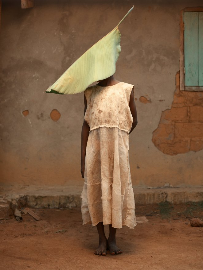 A young Congolese woman in a pink dress stands in front of a brick house, wearing a large banana leaf over her head