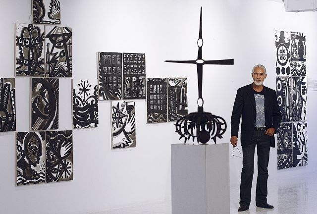 A middle-aged Haitian man in a dark suit jacket and jeans stands in front of an exhibit of his black and white abstract artwork