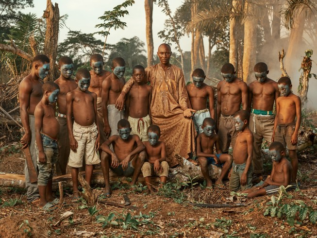 A Congolese man in an orange robe stands in the forest.  He's surrounded by 15 young boys with green paint on their faces
