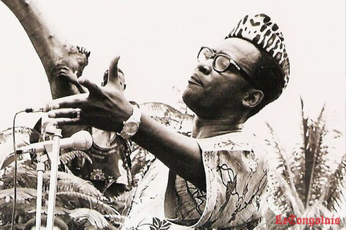 In a black and white photo, Mobutu stands in front of a microphone wearing a printed shirt, dark-rimmed glasses and his trademark leopard skin pillbox hat