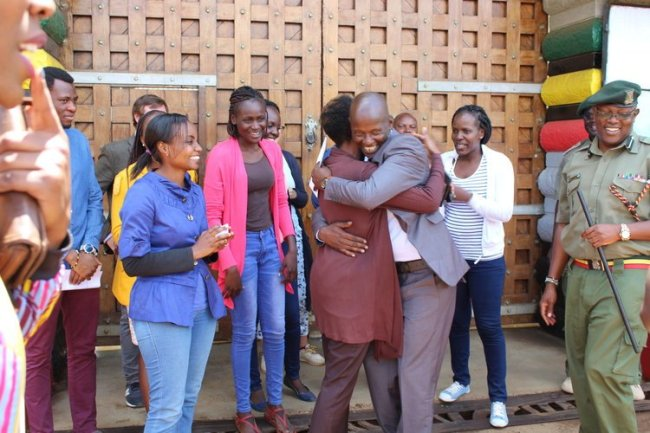 A Kenyan man hugs a woman, with several other smiling people standing around behind him