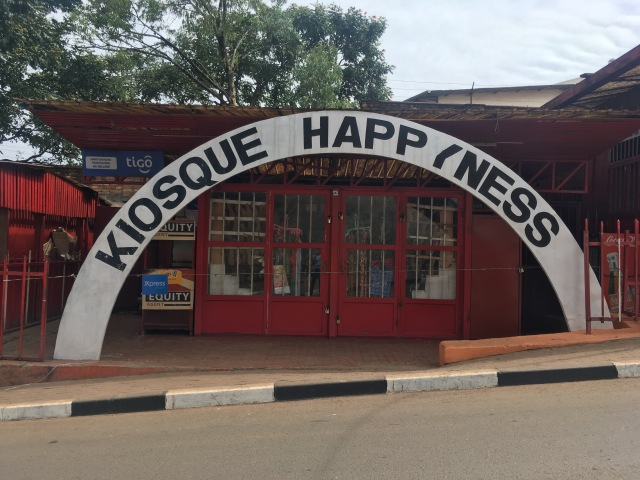 "A shop with an arched sign in front saying ""kiosque happiness"""