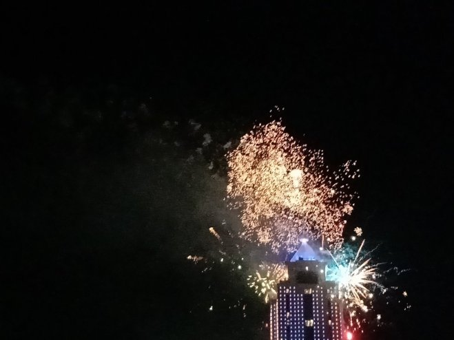 A skyscraper with fireworks exploding behind it