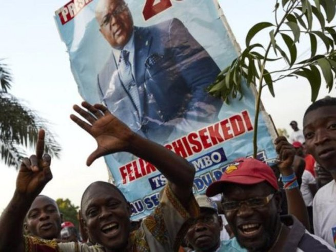 Several young Congolese men hold up a poster of Felix Tshisekedi