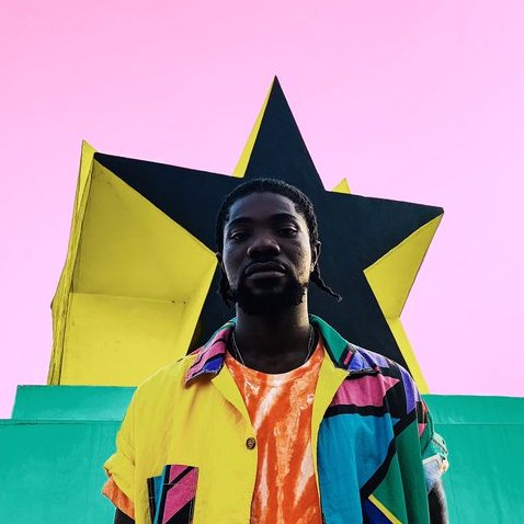 A young Ghanaian man in a colorful jacket standing in front of a black star against a pink background
