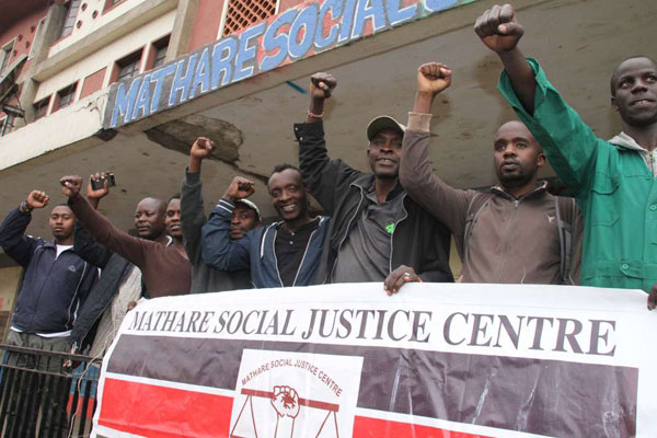 A group of Kenyan men with their fists raised stands in front of a building, holding a sign that says Mathare Social Justice Centre