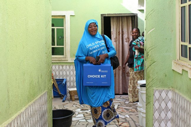 """A Nigerian woman in a blue hijab printed with the words """"child spacing saves lives"""" holds a blue box labeled """"choice kit,"""" in the courtyard of a house with green walls"""