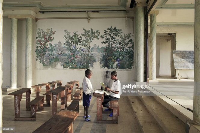 Two young boys sit at wooden desks inside an ornate, palatial room