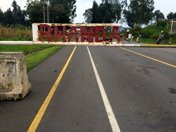"A white metal bar with raised red letters spelling ""Rwanda"" on it, in front of a paved road"