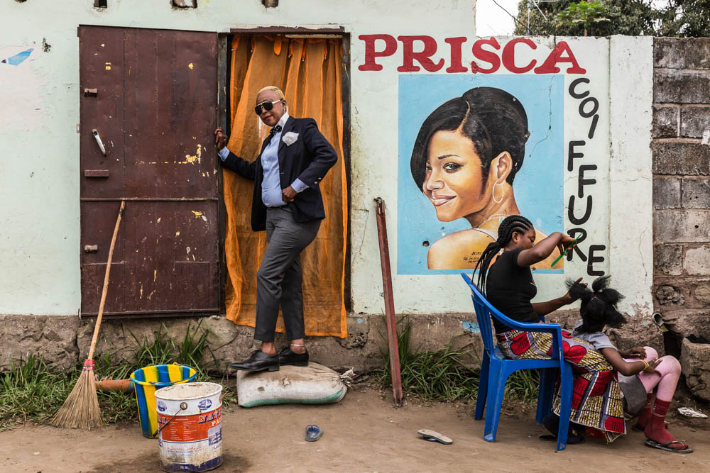 A woman in a suit poses next to a large sign for Prisca Coiffure, with another woman sitting in a chair braiding a girl's hair in front of the sign