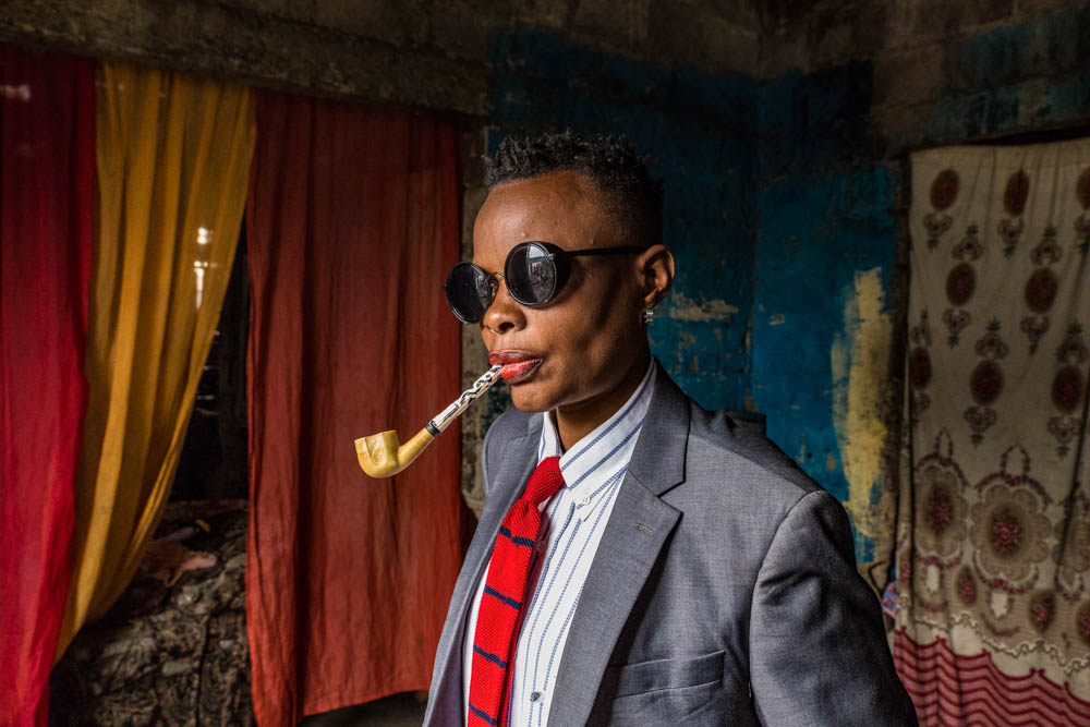 A woman in a suit and dark sunglasses with a traditionally carved wooden pipe in her mouth
