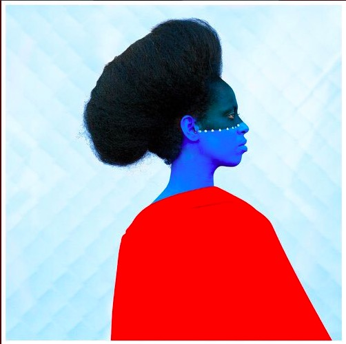 An Ethiopian woman with the bottom half of her face painted blue, wearing a red cape, in front of a blue background
