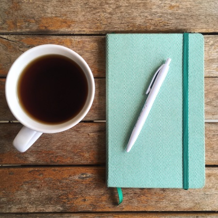 A green journal with a pen on top of it sitting next to a cup of tea on a wooden table
