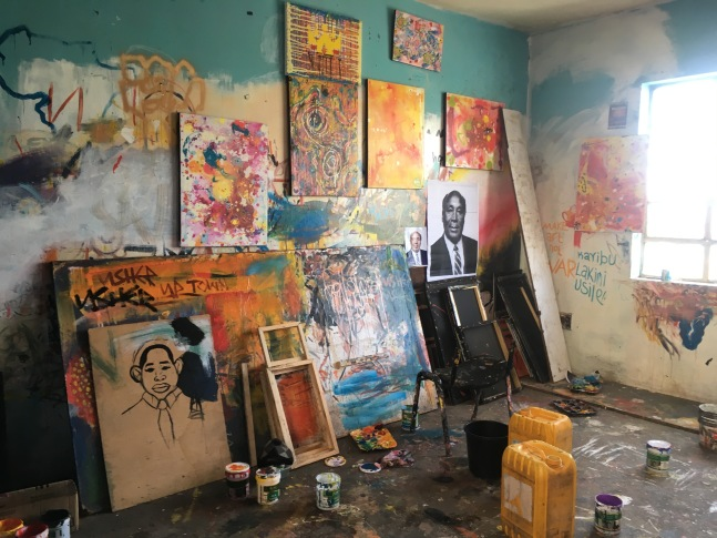 A room crowded with paintings on the walls and floor