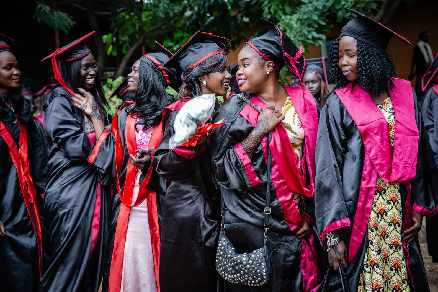 A group of young Sudanese women in black and red graduation regalia