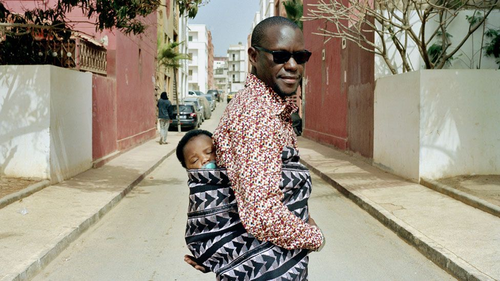 A Sengalese man carrying a sleepy baby on his back