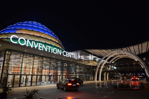 "A gleaming building with the words ""Convention Centre"" written on it, and a sort of beehive-like structure on top lit up in blue and yellow"