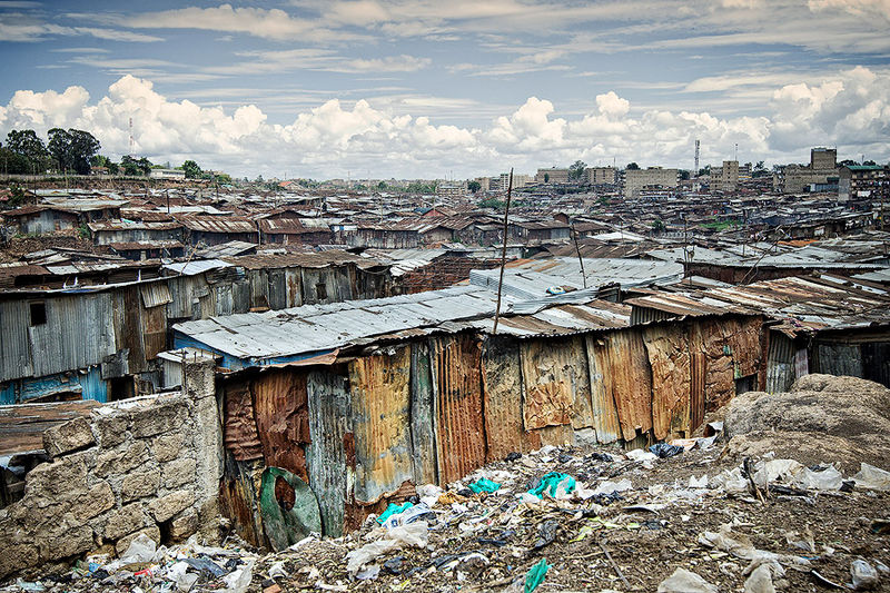 A large plot of houses made of tin, with rubbish on the ground in front of them