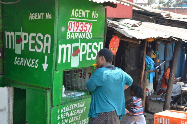 A Kenyan woman stands in front of a green kiosk with the word MPesa prominently painted on it