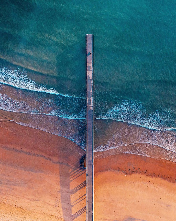 A long pier stretching out into the sea, viewed from above
