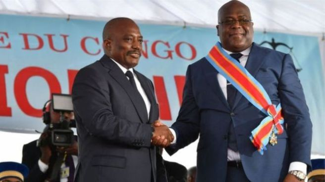 Joseph Kabila shakes hands with Félix Tshisekedi, who is wearing a red, blue and orange sash tied around his chest